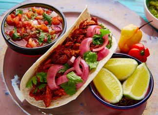 La cochinita pibil se acompaña de cebolla roja y limón. Foto cortesía.
